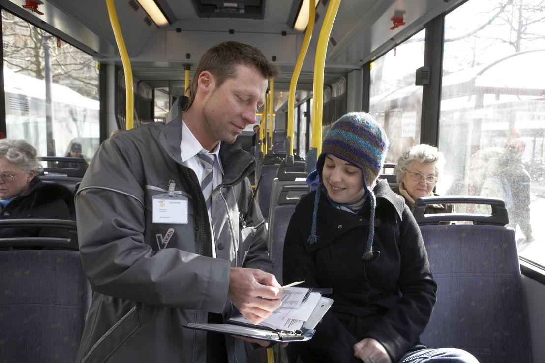 Een controleur van De Lijn kijkt na of een reiziger een geldig vervoerbewijs heeft.