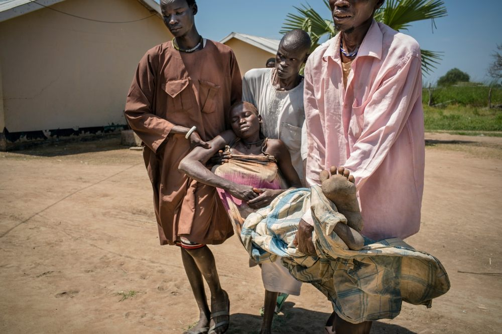 System identifier<br/>: MSF154655<br/>Title<br/>: Seeking malaria treatment around Aweil, South Sudan<br/>Photographer / cameraman<br/>: Diana Zeyneb Alhindawi<br/>Countries:<br/>South Sudan. Description:32-year-old Arek Nuoi, mother of four, receives an IV treatment of quinine for malaria after she was brought to Panthou government health care center unconscious, carried on a bicycle by her three brothers-in-law. &quot;Yesterday, we were here [in Panthou] for market day, and she was okay,&quot; said one of her brothers-in-law. &quot;Last night she had a headache and then body pain,&quot; continued her mother. &quot;This morning, I went to collect the local tree,&quot; she explained, referring to the traditional plant medicine for headaches and other pain. When she returned, she found Arek collapsed and vomiting. The family tied a chair onto a bicycle and placed Arek in the chair. They then pushed it all the way from their home village of Maper to the Panthou health center. The journey took one and a half hours. At home they have a mosquito net and always sleep under it, but none of them knew how malaria is contracted. Panthou health care center is the only one in Aweil South county and is currently treating about 150 malaria patients per day. They had just received a supply of ACT oral medication for malaria; their previous stock had run out on August 17. The new stock will likely run out in one or two weeks. They have quinine, but not a lot, so they reserve it for serious cases. They have no RDT (rapid detection tests), so diagnosis is only done clinically, based on observed symptoms.