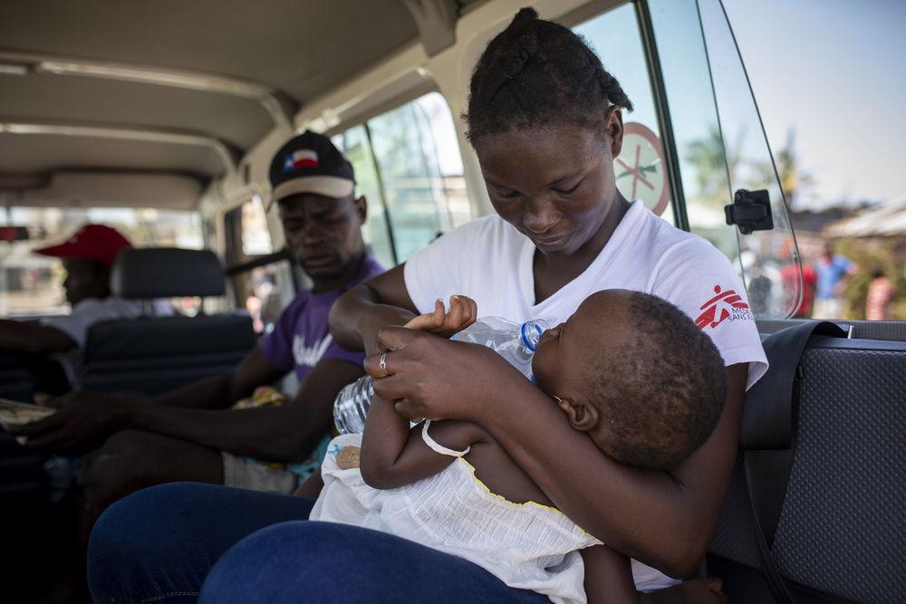 Aida Joao, educadora de pares de MSF, evacúa a un niño con posible neumonía desde el barrio de Praia Nova al centro de Salud de Punta Gea. © Pablo Garrigós / MSF