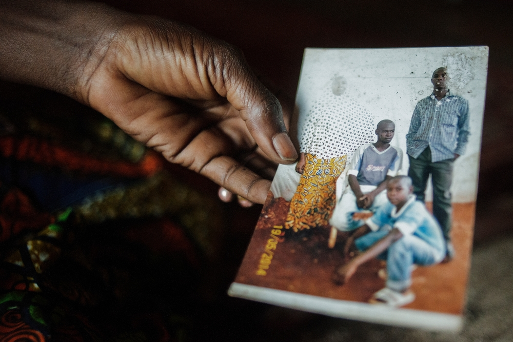 """MSF159645<br/>Alima shows a photograph of her son, Amousa who was 23 years old at the time of his death (right, 1st row)<br/><br/>He was treated at the Red Cross Center after he became ill due to the living conditions in the camp.<br/><br/>Alima is trying to cope by relying on the help of other people living with her in the camp, as she and her husband are unemployed. """"We were born here, our parents and grandparents too... and now we are treated as strangers&quot;."""