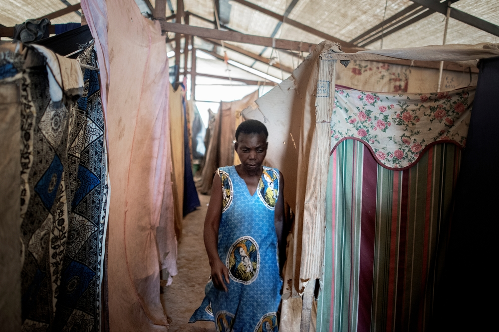 MSF159669<br/>45 year old Julienne walks inside a shelter at a displaced persons camp in Benzvi, Bangui.<br/><br/>Julienne has lived in Benzvi camp for one year but it has been two years since she left her arrondissement near KM5 in Bangui. An armed group came into her house but she escaped with her seven children, her husband and her grandson. While they were fleeing, her grandson was shot and died, just as they arrived in the camp of Saint Jacques. They stayed more than a year in this structure but they finally decided to move again because of lack of space in the church. She has to look after children on her own. In order to survive, she receives food rations from NGOs. <br/>Julienne doesn't want to return to her neighbourhood. Her house was burned and looted and her safety cannot be guaranteed.