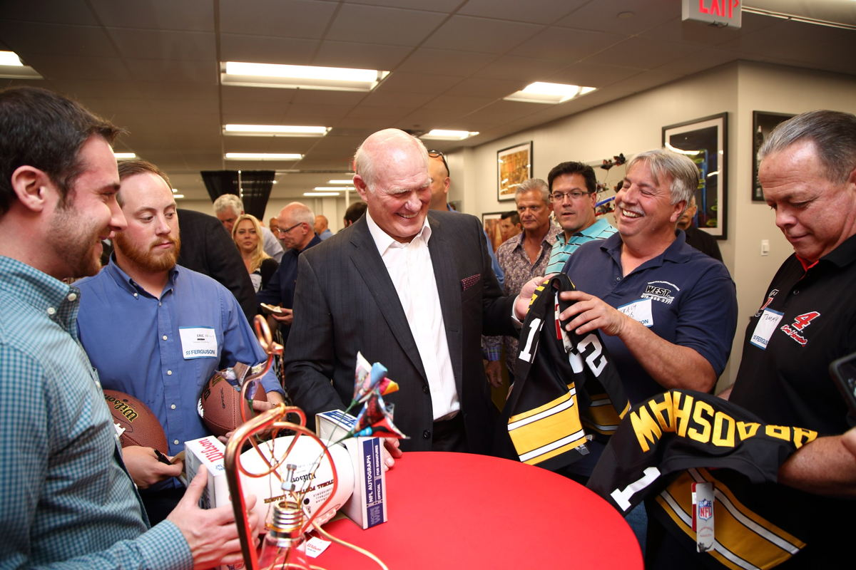 Bradshaw laughs with Ferguson customers.
