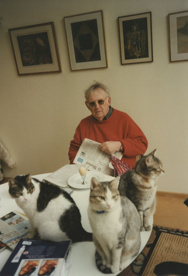 Hugo Claus met drie poezen op de ontbijttafel.