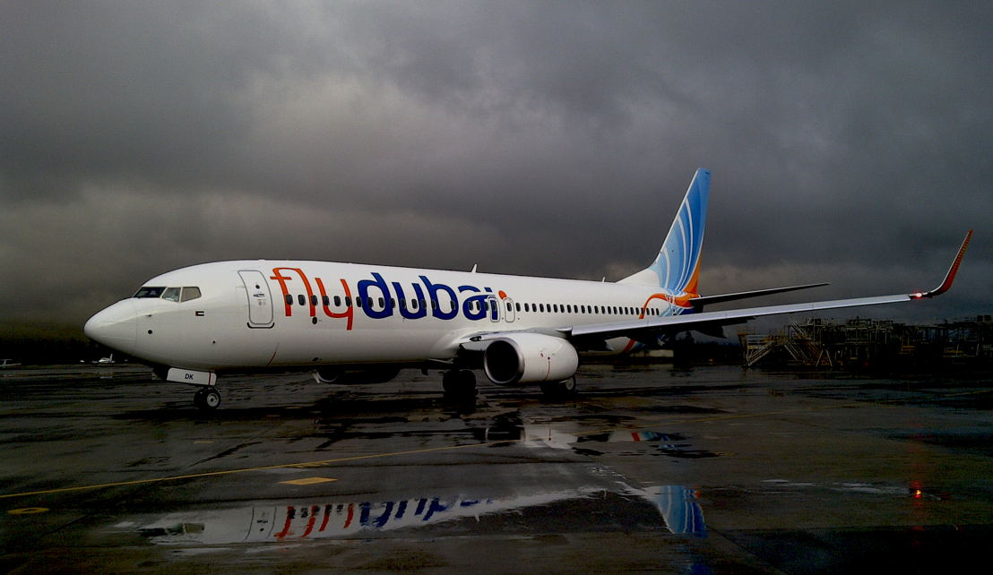 Aircraft on the ground on a wet day with reflection in puddle