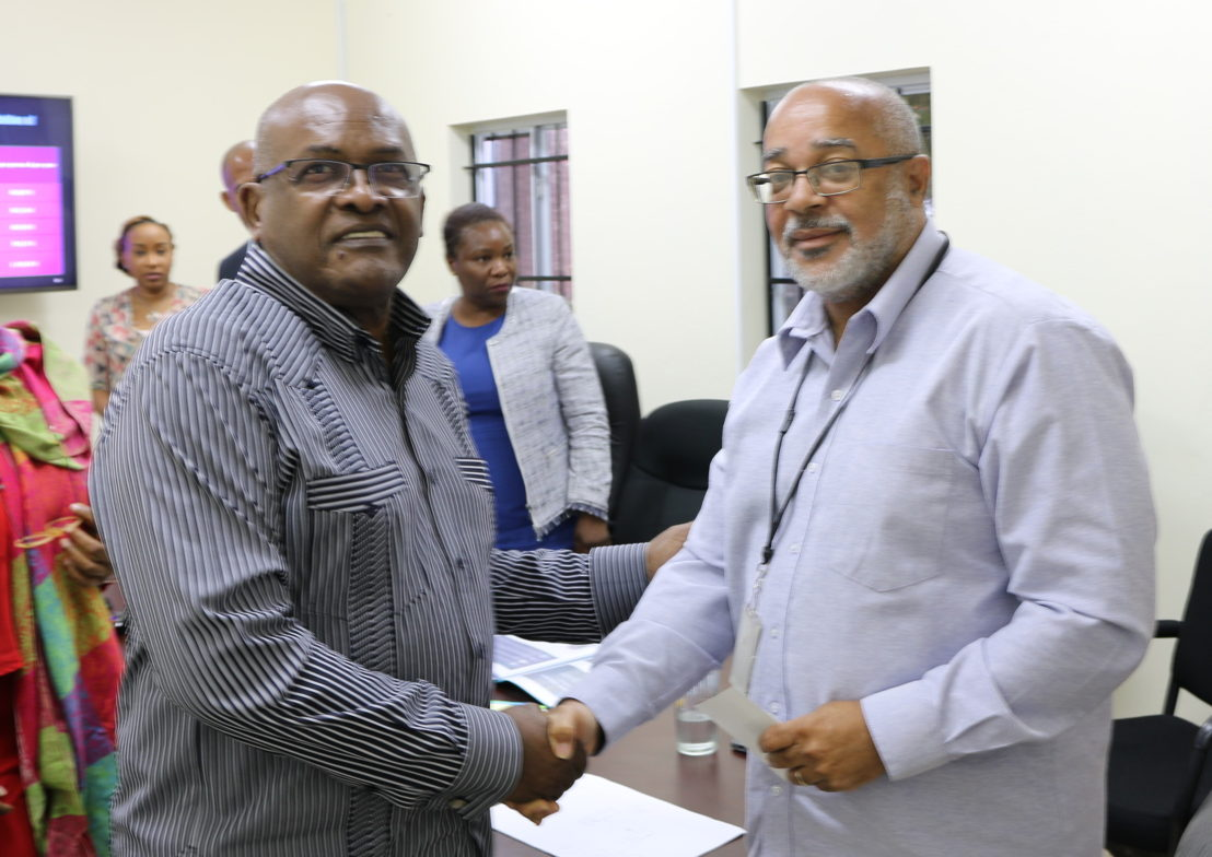OECS Director General, Dr. Didacus Jules and CGSS General Director, Mr. Henri Yacou, shake hands at the CGSS visit to OECS Headquarters in June 2018.