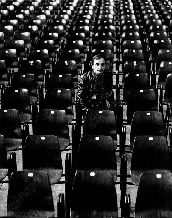 Charles Aznavour is sat down in the stalls of a empty theatre. Milan, 1974.<br/>AKG1734624