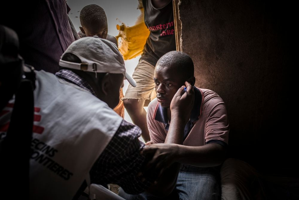 An MSF health worker communicates with an HIV-positive man who became deaf and blind after he stopped taking his antiretroviral drugs due to social stigma. MSF teams go door-to-door to test people for HIV in Katwe, Uganda. Photographer: Guillaume Binet/MYOP
