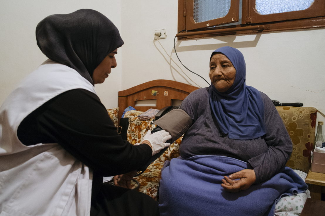 "MSF nurse Amal is helping Amira Al-Hassiri, 80. She has been bedridden for seven years and suffers from diabetes and high blood pressure. ""They always visit me and measure my diabetes level and blood pressure. God bless them,"" says Amira. Photographer: Bruno De Cock"