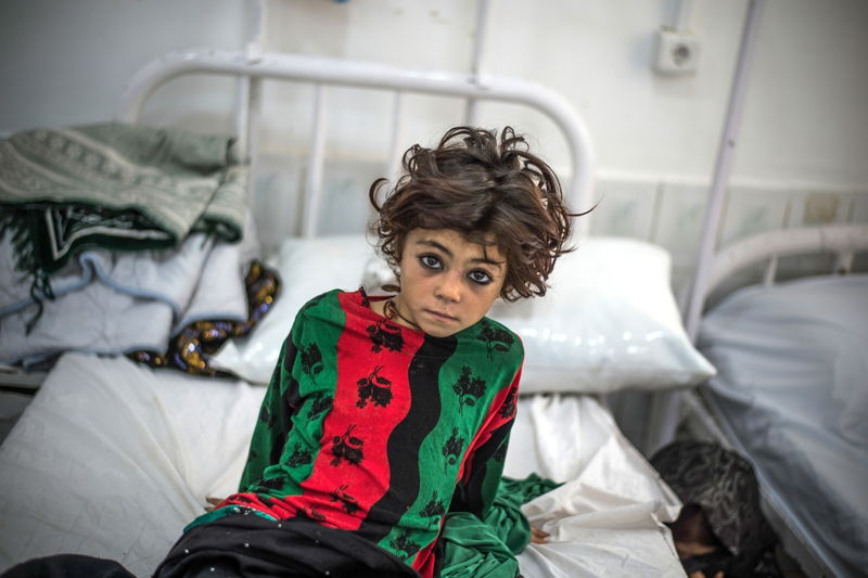 A girl waits in the emergency room of Boost hospital, Lashkar Gah, in Afghanistan's Helmand province, which MSF runs alongside the Afghan Ministry of Health. Photographer: Kadir Van Lohuizen/Noor