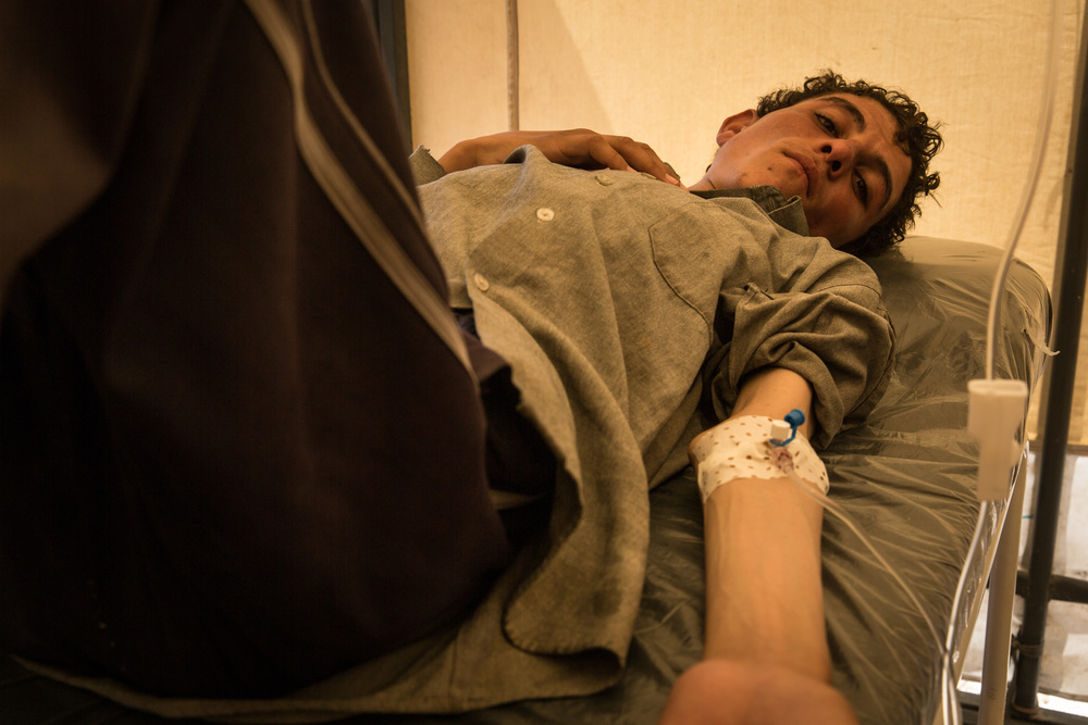 Syria - Kurdish province - Aïn Issa displaced camp. MSF Clinic. A Syrian from Raqqa is perfused under the eyes of his worried father. Photographer: MSF-FRANCE