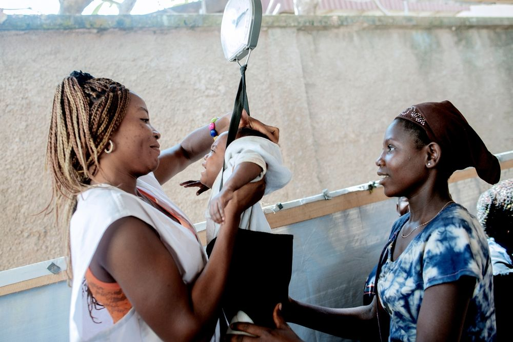 MSF159663<br/>17 year old Mireil has her baby weighed by a Medecins Sans Frontiers (MSF) staff member at an MSF hospital at a displaced persons camp in Benzvi, Bangui