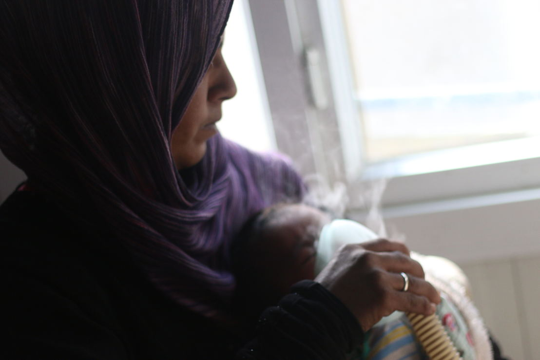 A mother gives her baby treatment on a nebulizer in this picture taken in MSF's hospital on March 18th in Azaz district in Aleppo governorate, northern Syria. On April 18th MSF warned that the situation was critical for more than 100,000 people who were trapped by renewed fighting in the area, and called on all warring parties to respect civilians and health structures. Photographer: Mahmoud Abdel-rahman