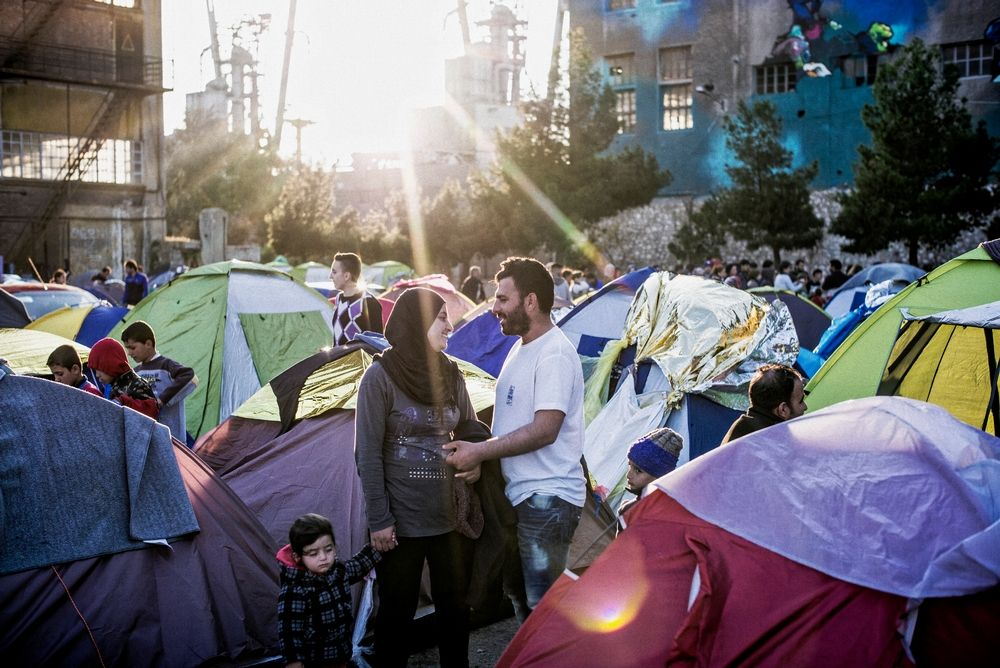 A couple share a moment in the sunlight in a makeshift refugee camp set up in the shadow of the docks in Piraeus, near Athens. Some 5,000 people who intended to travel north found themselves stuck in the Greek capital when the Former Yugoslav Republic of Macedonia closed its borders in March. Photographer: Guillaume Binet/MYOP