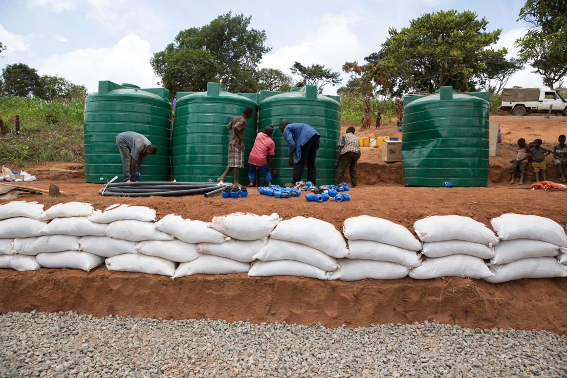 People queue outside a water storage and pump facility built by Medecins Sans Frontiers (MSF). Over 5.800 Mozambican nationals have camped in the village of Kapise 2 in Malawi after fleeing their homes in Mozambique. The only regular water source in the village has ran dry and the only way to get water is from few pre-existing sources and the two additional boreholes respectively rehabilitated and constructed by MSF. Even then, waiting times times up to 2.5 hours at the water pump and with the continuous influx of people, the capacity of the borehole today can only provide around 8 liters of water per person per day, well below the minimum humanitarian standards of 15-20L. © James Oatway / MSF