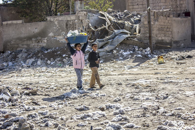 Two kids helping their parents clear the rubble from their house. Al Mishlab, east of Raqqa city. Credit: Diala Ghassan/MSF