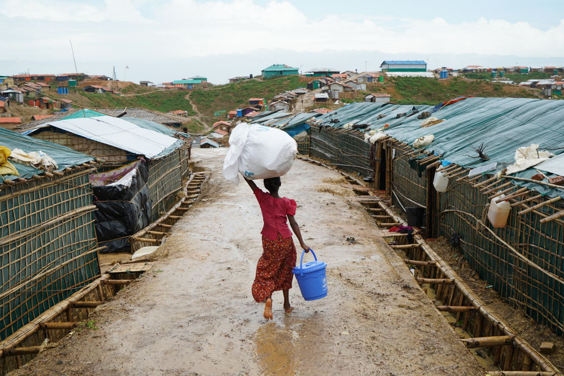 A girl carries a water bucket and other relief items donated by the UN through the wet streets of Balukhali camp. The monsoons have caused havoc in the camps and for local communities, resulting in landslides, floors and fires, and have led to injuries, deaths and the destruction of infrastructure and facilities. Water supplies have become contaminated with dirty water/human waste, posing a public health risk. One year on since the biggest influx of Rohingya refugees to Bangladesh, the Rohingya face an uncertain future. Overcrowding and congestion are major issues in the camps, access to safe drinking water and sanitation services is insufficient, and the Rohingya suffer from a lack of formal legal status,. Photographer: Dalila Mahdawi