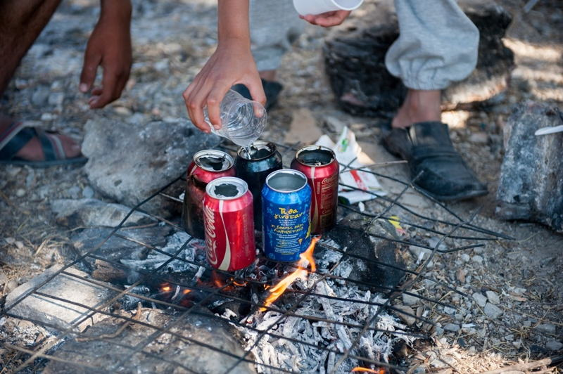 Photographer: Georgios Makkas<br/><br/>Caption: Syrian refugees use empty cans to boil water make tea in Kara Tepe camp.