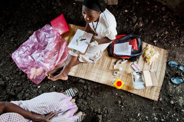 Lokale gezondheidswerkers als Nelisiwe Ziqugu leggen lange afstanden lopend af om mensen van deur tot deur te testen. KwaZulu-Natal, Zuid-Afrika – juli 2013. © Peter Casaer/MSF