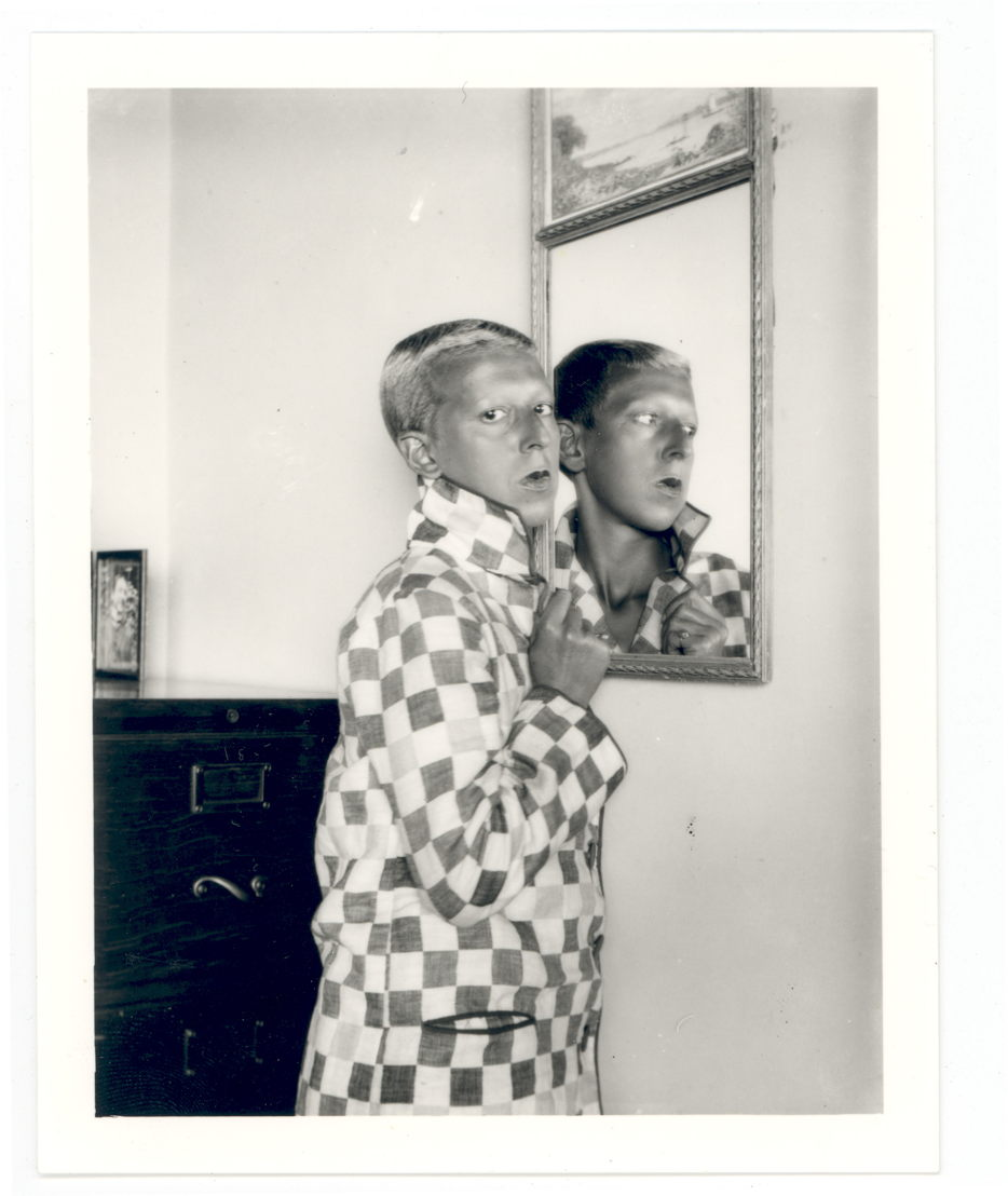 Self-portrait (reflected image in mirror, checqued jacket) by Claude Cahun, 1928. Jersey Heritage Collections © Jersey Heritage
