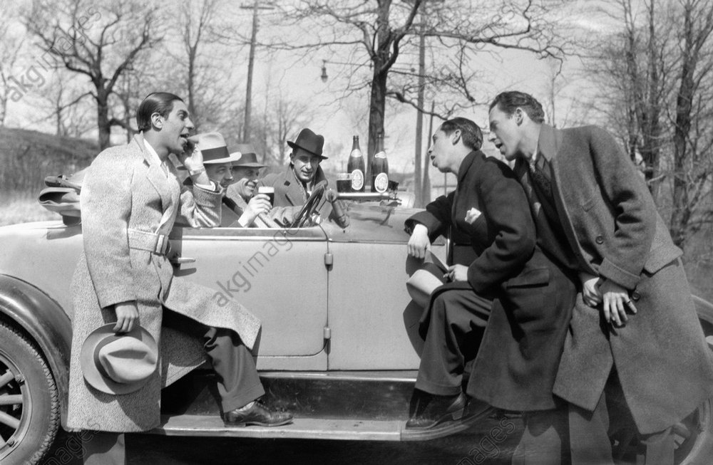 A group of men standing in front of and sitting in a convertible car drinking beer, New York.<br/>Photo, 1928<br/>AKG1046022