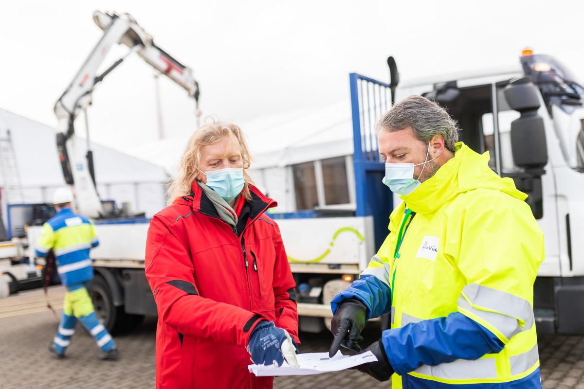 Een medewerker van de stad Antwerpen overlegt met Fluvius  waar de extra mobiele verdeelkasten op Park Spoor Oost moeten komen.