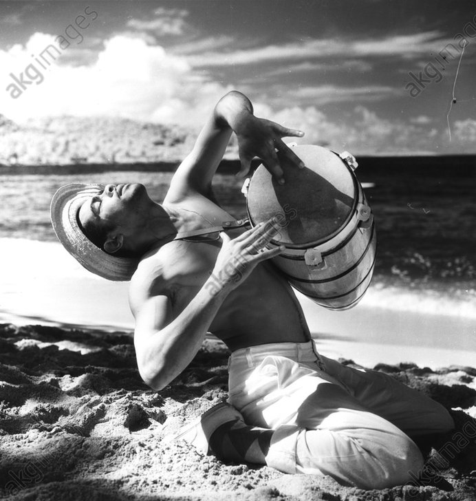 Calypso Drummer on the beach (Jamaica). Photo, January 1957 (Toni Frissell).<br/>AKG268898