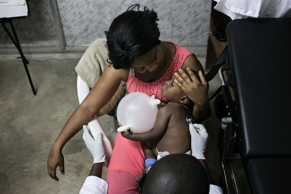 14 month old M'Bemba with his foster mother and aunt Fatoumata Eisse during a medical consultation with Dr Daouda Berete at the Medecins Sans Frontieres (MSF) health facility in Nongo, Conakry. Photographer: Albert Masias/MSF