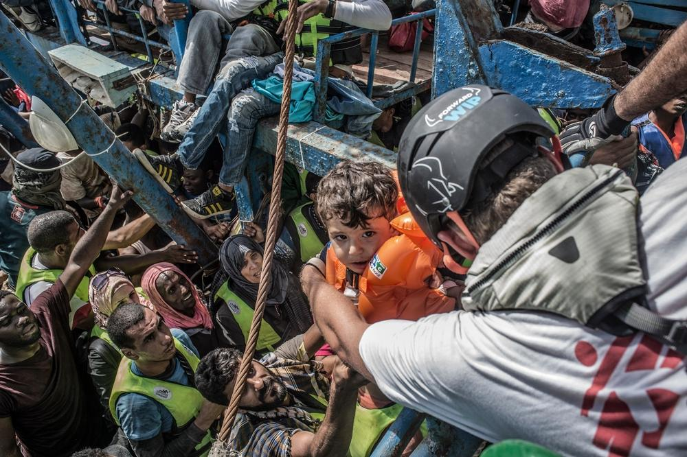 Photographer: Francesco Zizola<br/><br/>Caption:  26th August 2015. A young child is lifted from a boat containing approximately 650 people by Sebastian Stein (Doctors Without Borders / MSF Coordinator) during a rescue in the Mediterranean Sea
