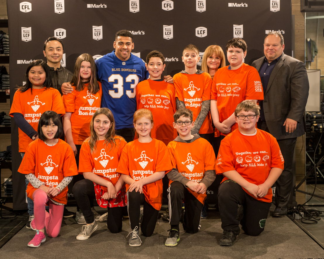 Jumpstart kids with David Lui (Vice-President of Marketing, Mark's), Andrew Harris (running back, Winnipeg Blue Bombers), Christina Litz (Chief Marketing, Digital and Strategy Officer, CFL), and Wade Miller (CEO and President of the Winnipeg Blue Bombers). Photo credit: Reid Valmestad/CFL