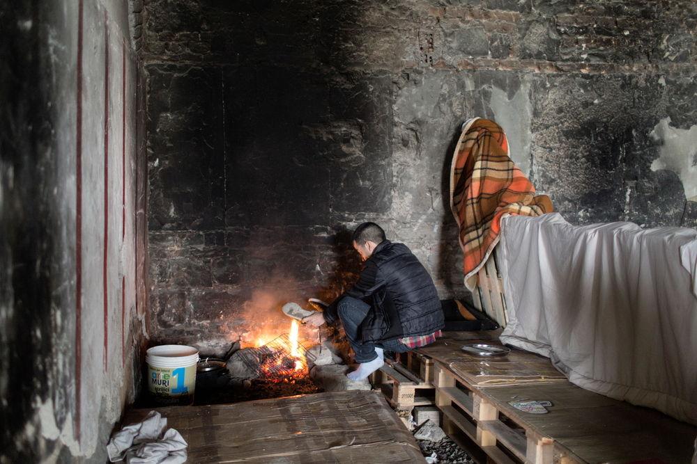 Triëst, een asielzoeker warmt zich op aan een vuurtje in een verlaten stationsruimte.  © Alessandro Penso/Maps