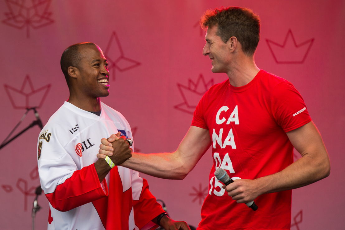 Henry Burris and Dan Snow shake hands on the main stage. Photo Credit: Jim Ross/CFL